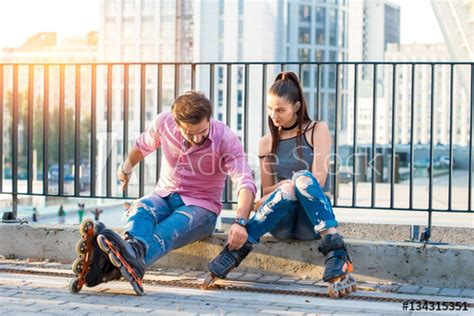 """""""Young couple on rollerblades sitting"""